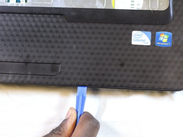 Using a plastic opening tool to lift the sides of the cover.