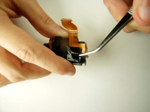 With the tweezers remove the black tape to detach the chip from the lens box.