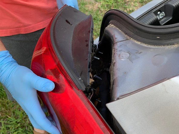 Once the wires are disconnected facing the bumper, firmly grasp the entire plastic casing of the tail light and pull directly towards your hips in order to not catch the hidden clip located on the side of the car near the end of the tail light casing.