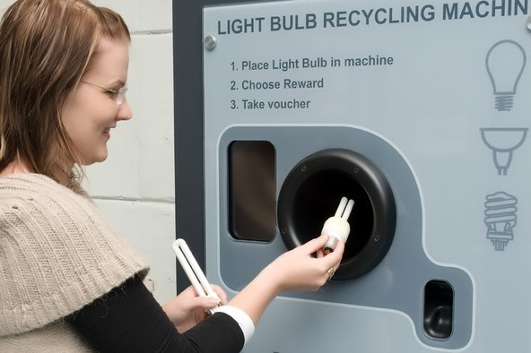 Woman using a reVending machine to recycle her light bulbs