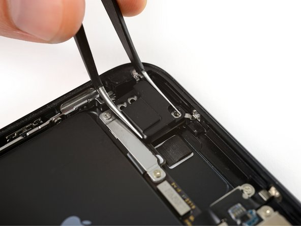 The screw boss at the top of the antenna component is tucked into a small recess in the top edge of the iPhone.