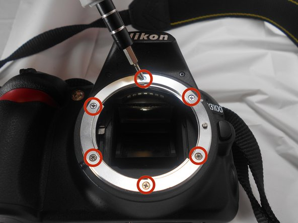 Remove the 6 Phillips screws on the front of the lens mounting ring.