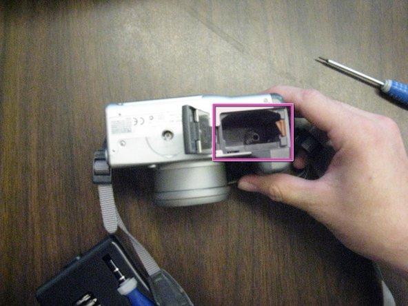 On the bottom of the camera, push and slide open the battery compartment.
