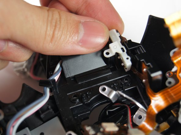 Gently lift out the tiny circuit board with your hands. A metal frame and a tiny side attachment should come off too.