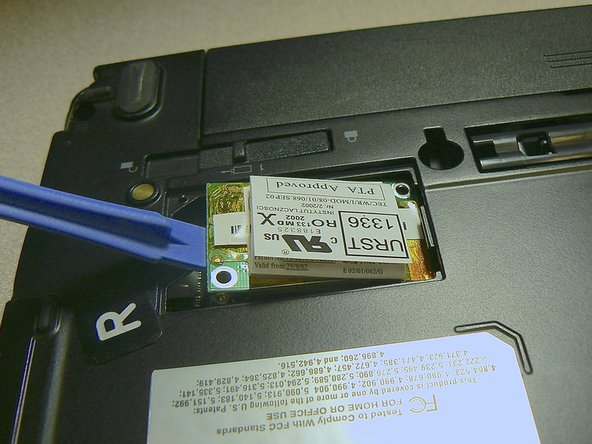 Use a plastic opening tool to gently lift the wireless card out while leaving the wire connected.