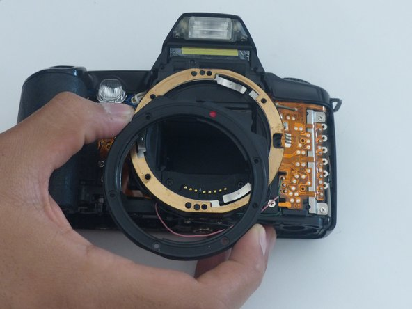 Simply using your fingers - although you can use something else such as tweezers - remove the first layer of the lens mount. This first layer is black, plastic, has a red dot at the top, and so on.
