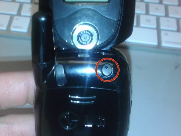Using a spudger or plastic opening tool, pry off the screw cover near the phone's antenna.