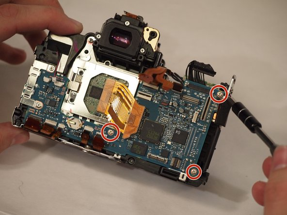 Remove the two screws on the right side of the motherboard as well as the screw in the center.