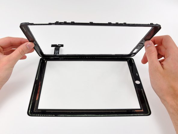 Remove the display frame from the front glass, being careful not to rip the digitizer cable in the process.