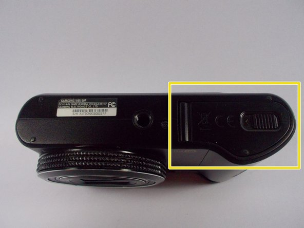 Flip the camera upside-down so that the compartment with the battery and memory card is facing you.