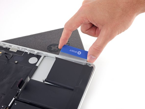 Slide the card farther underneath the battery cell to separate it from the adhesive securing it to the MacBook Pro's upper case.