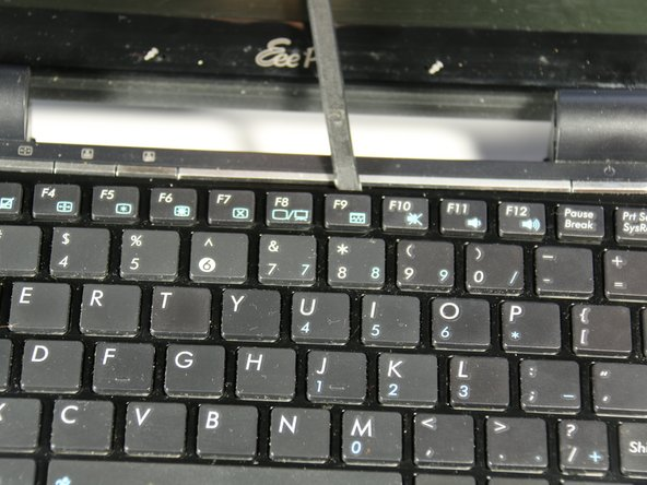Identify the four connection points holding the top of the keyboard to the main body of the netbook. To remove the keyboard, use the spudger to unhook the keyboard upwards at these points.
