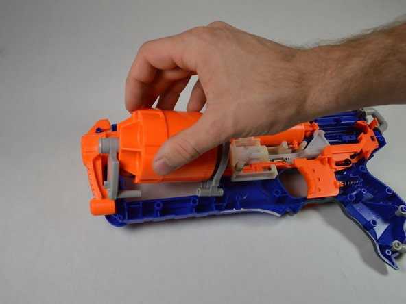 To make the relevant pieces accessible, remove the barrel from its position on the bottom half of the blaster cover.