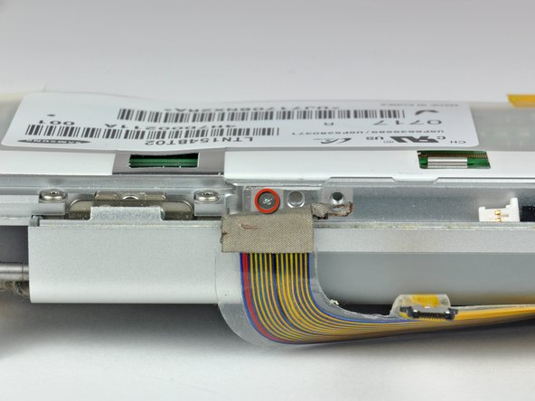 Image 1/1: Remove the Phillips screw hidden behind the display data cable.
