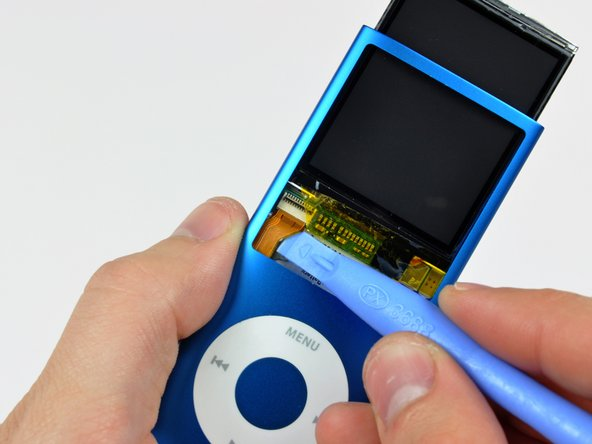 Use an iPod opening tool to peel the display data cable off the thin metal plate attached to the display.