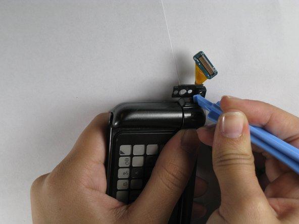 Déplacez la moitié supérieure de la charnière avec l'outil d'ouverture en plastique. Cela libèrera le couvercle de charnière pour le retrait.