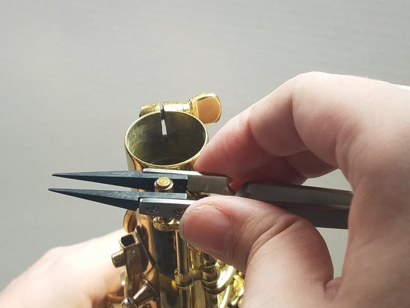 Using your needlenose pliers, or in the case of this guide the iFixit reverse tweezers, very carefully bend the octave pin either towards or away from the body of the saxophone, depending on how it is misaligned.