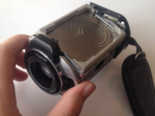 Lift the hard drive out of the camera by grasping the grey rubber mounting brackets and pulling them upwards.