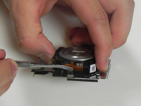 Use a nylon or metal spudger to release the lens.