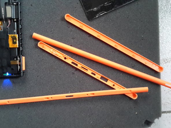 first remove the orange (or other colour) bezels from the side of the tab. the all have a small hole grip.