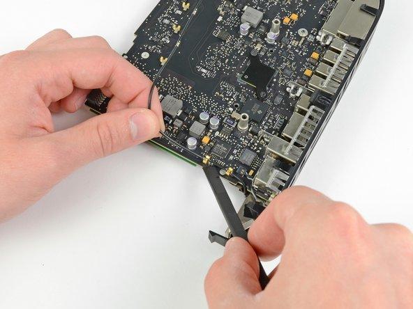 Fädle das Antennenkabel aus den Halteklammern auf dem Logic Board in der Nähe der I/O Blende.