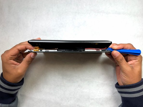 Using the plastic opening tool, work your way along the edge of the tablet.