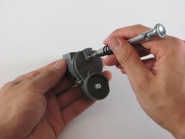 Image 1/3: Carefully pry the gear box open by placing a flat head screwdriver in the slot