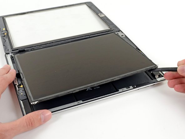 Image 1/3: Rotate the LCD along its left edge and lay it down on top of the front glass panel.