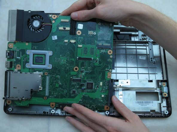 Use your hands to gently lift the top right side of the motherboard. Then, pull it upwards to the right and away from you.