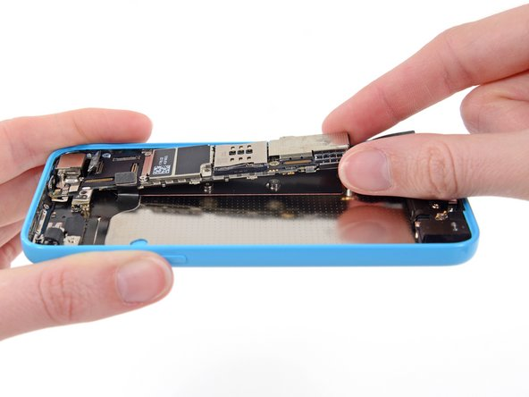 Holding the phone level, lift the bottom end of the logic board up enough to grasp it with your fingers.