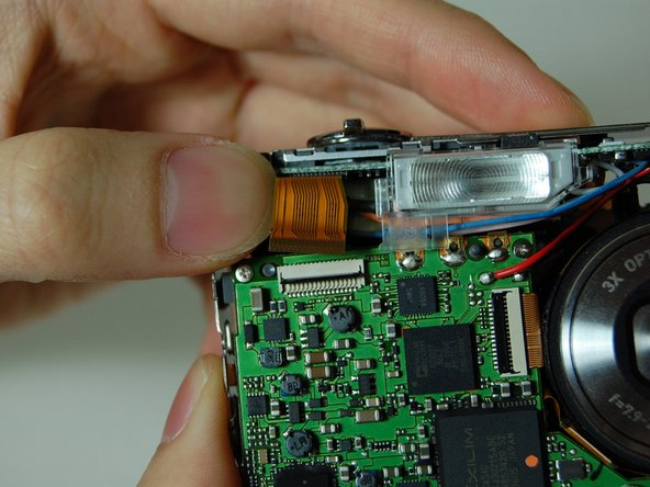On the front of the camera, near the flash flip the connector holding the ribbon.
