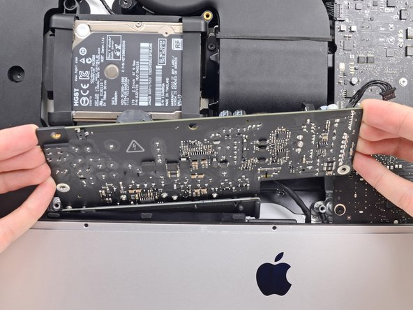 Do not try to completely remove the power supply from the iMac yet—it is still connected to the logic board.