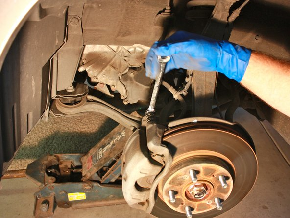 Using a 12 mm wrench or socket, remove the two caliper mounting bolts.