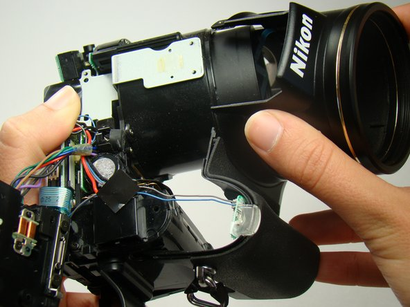 Image 1/3: Be sure that the front cover is not attached to anything or caught on anything when pulling it away from the rest of the camera.