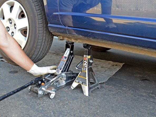 Image 1/3: Lift up the lever on the jack stand to lower its saddle column, and remove the jack stand from under the car.