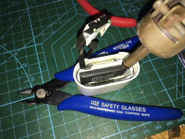 继续用热风枪加热后,用撬棒将电池松动部分把连接排线从固定底座上的压扣松动,取出电池