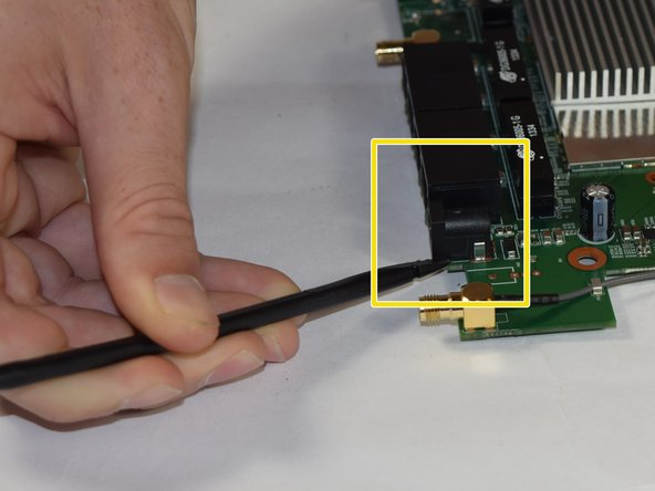 Image 3/3: Use a black spudger to gently separate the power port from the motherboard