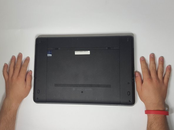 Turn the computer upside down on a flat side, so that you are seeing the underside of the laptop.