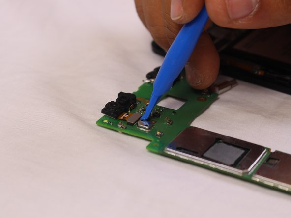 Use a plastic opening tool to pry up the camera connector from the motherboard.