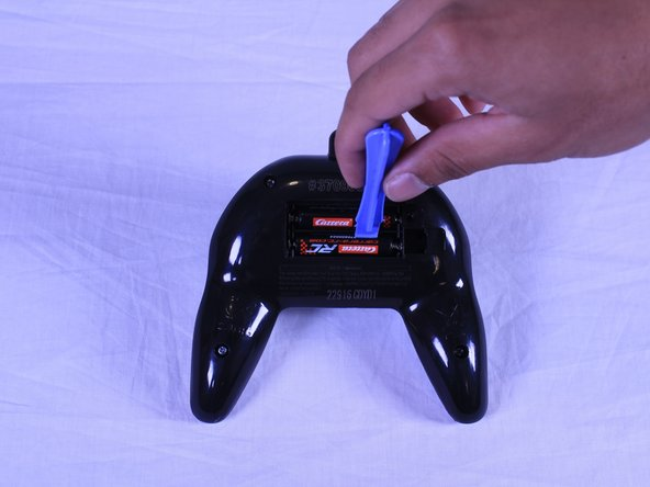 Use the plastic opening tool to remove the battery cover and the batteries.