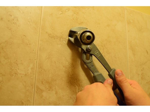 Do this by turning the arm counter-clockwise until it releases from the wall.