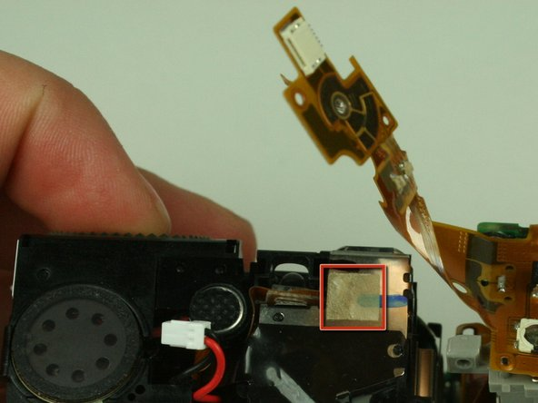Adhesive tape attaches the flex circuit to the top of the camera. Gently un-stick the flex circuit from the tape, but do not completely remove the flex circuit.