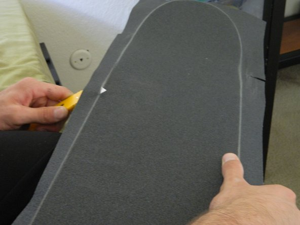 Angle your knife towards the inside of the skateboard to make it easier to cut a straight line.