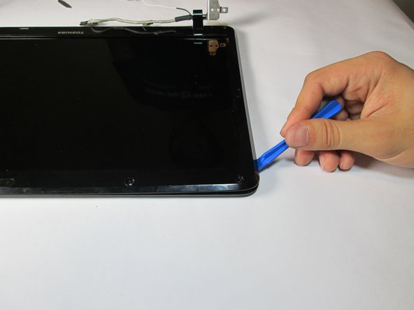 Use the plastic opening tool to pry the screen housing.