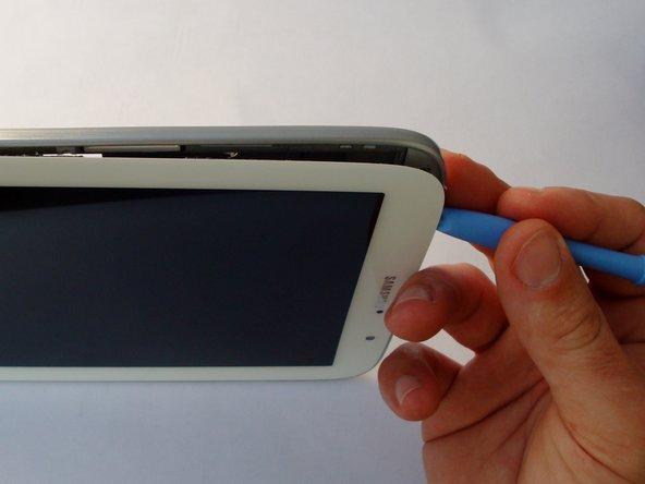 Setze ein Plastiköffnungswerkzeug zwischen silbernem Rahmen und der Scheibe ein, beginne oben am Tablet.