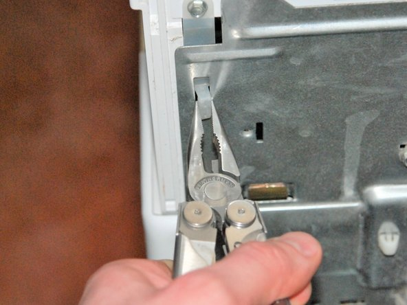 Pinch the plastic tabs with the needle nose pliers and push through the metal back panel.