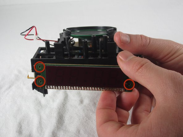 Applying a bit of pressure at each of the contact points (illustrated by red circles), disconnect the display from the plastic housing.