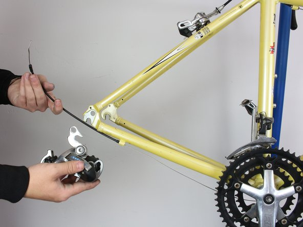 Using a hex key wrench, unscrew the bolt that fastens the derailleur to the bike frame. The derailleur should come off easily because it is no longer fastened to the bike and the derailleur cable can easily slip out.