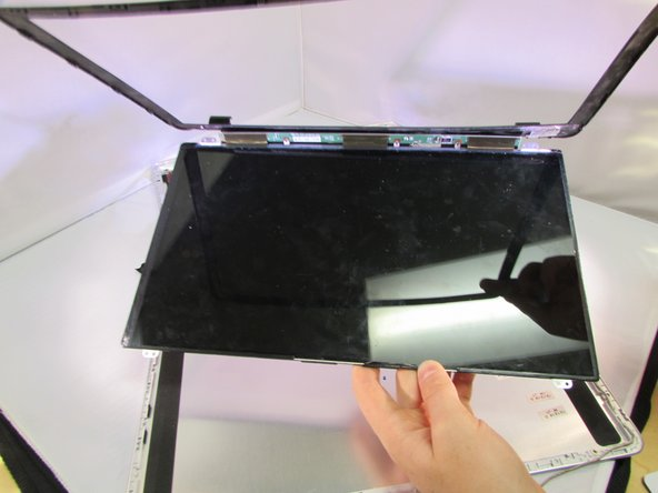 Image 2/2: Lift the screen and frame out of the computer body.