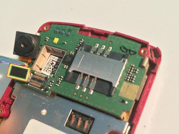 Remove the camera by releasing the ribbon cable connection with a plastic spudger, then pulling it out with tweezers.